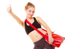 Sport. Fitness girl with gym bag showing thumb up Stock Photography