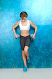 Sport fitness girl near a blue wall Stock Photography