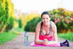 Sport fitness girl training push-ups. Female athlete exercising push up outside in empty park. Fit model in crossfit stock photography