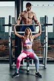 Sport, fitness, groepswerk, het bodybuilding en mensenconcept - jonge vrouw en persoonlijke trainer met barbellverbuiging stock afbeelding
