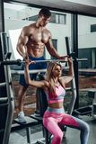 Sport, fitness, groepswerk, het bodybuilding en mensenconcept - jonge vrouw en persoonlijke trainer met barbellverbuiging stock foto's