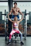 Sport, fitness, groepswerk, het bodybuilding en mensenconcept - jonge vrouw en persoonlijke trainer met barbellverbuiging stock fotografie