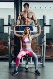 Sport, fitness, groepswerk, het bodybuilding en mensenconcept - jonge vrouw en persoonlijke trainer met barbellverbuiging royalty-vrije stock afbeeldingen