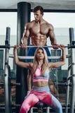 Sport, fitness, groepswerk, het bodybuilding en mensenconcept - jonge vrouw en persoonlijke trainer met barbellverbuiging royalty-vrije stock foto's