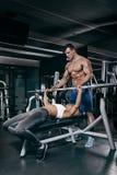 Sport, fitness, groepswerk, het bodybuilding en mensenconcept - jonge vrouw en persoonlijke trainer met barbellverbuiging stock foto