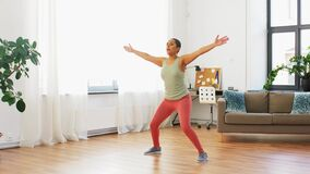 Woman doing jumping jack exercise at home
