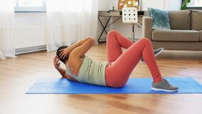 African woman making abdominal exercises at home