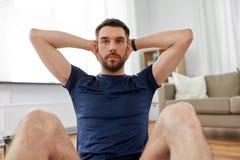 Man making abdominal exercises at home royalty free stock photos