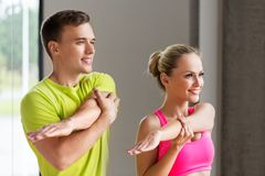 Smiling man and woman exercising in gym. Sport, fitness, healthy lifestyle and people concept - smiling men and women stretching in gym stock photography