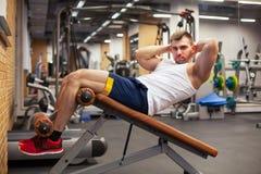 Sport, fitness, het bodybuilding, levensstijl en mensenconcept - jonge mens die zitten-op de buikpers van de oefeningenbank binne stock fotografie