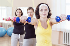 Sport and Fitness Ideas. Group of Three Caucasian Female Athletes Having a Workout Training with Barbells Indoors Royalty Free Stock Images