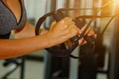 Sport, fitness, lifestyle and people concept - close lifestyle of young woman flexing muscles on cable gym machine