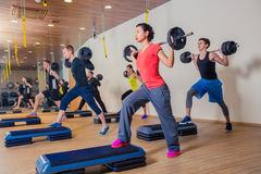 Sport, fitness, lifestyle and people concept. Group flexing muscles with barbells in gym stock photos