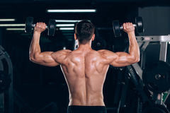 Sport, fitness, lifestyle and people concept - Muscular bodybuilder guy doing exercises with dumbbells in gym. Stock Photo