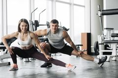 Sport, fitness, lifestyle and people concept - smiling man and woman stretching in gym. Sport, fitness, lifestyle and people concept - smiling men and women royalty free stock image