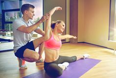 Smiling woman with male trainer exercising in gym. Sport, fitness, lifestyle and people concept - smiling women with male personal trainer exercising in gym Royalty Free Stock Image