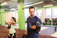 Man and woman with kettlebell exercising in gym. Sport, fitness, lifestyle and people concept - women with kettlebell and men with dumbbell exercising in gym Stock Photography