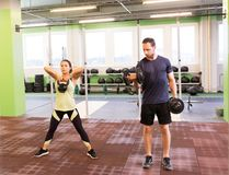 Man and woman with kettlebell exercising in gym Royalty Free Stock Photo