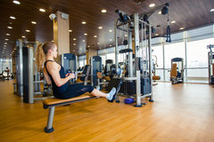 Sport, fitness, lifestyle and people concept -. Sport, fitness. lifestyle and people concept - young woman flexing muscles on gym machine stock images