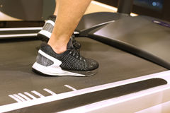 Sport, fitness, lifestyle, technology and people concept - close up of men legs walking on treadmills in gym Stock Images