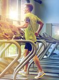Man with smartphone exercising on treadmill in gym. Sport, fitness, lifestyle, technology and people concept - man with smartphone and earphones exercising on Royalty Free Stock Image