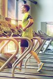 Man with smartphone exercising on treadmill in gym. Sport, fitness, lifestyle, technology and people concept - man with smartphone and earphones exercising on Stock Photography
