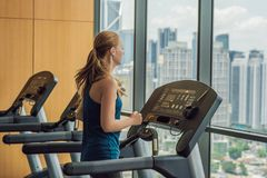 Sport, fitness, lifestyle, technology and people concept - woman exercising on treadmill in gym against the background stock photo