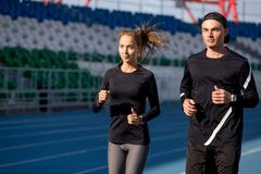 Sport and fitness. loving ouple running on arena track. Morning workout in the arena area. competing men and woman stock photos