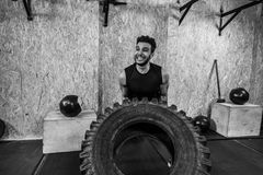 Sport Fitness Man Flipping Wheel Tire Crossfit Training. Young Healthy Guy Gym Interior Royalty Free Stock Photos