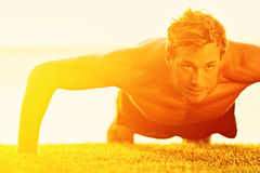 Sport fitness man push-ups. Male athlete exercising push up outside in sunny sunshine. Fit shirtless male fitness model in crossfit exercise outdoors. Healthy Stock Images