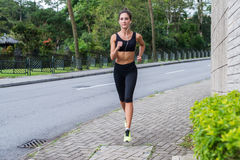 Sport fitness model jogging on sidewalk in quiet city district. Female athlete training outdoors. Sport fitness model jogging on sidewalk in quiet city district Royalty Free Stock Images