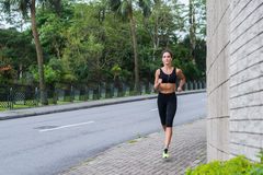 Sport fitness model jogging on sidewalk in quiet city district. Female athlete training outdoors. Sport fitness model jogging on sidewalk in quiet city district Stock Photos