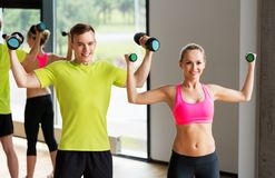 Couple with dumbbells exercising in gym royalty free stock photos
