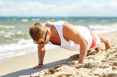 Young man doing push-ups on summer beach. Sport, fitness and people concept - happy young man in sunglasses exercising and doing push-ups on summer beach Royalty Free Stock Image