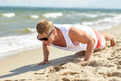 Young man doing push-ups on summer beach Royalty Free Stock Photo