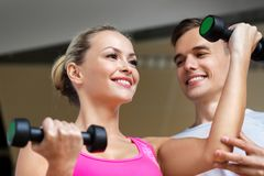 Woman with dumbbells exercising in gym royalty free stock photo