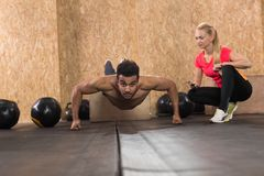 Sport Fitness People Crossfit Training, Young Healthy Hispanic Man Do Push Ups Woman Trainer. Gym Interior royalty free stock image