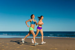 Sport and Fitness - people jogging on beach Royalty Free Stock Photography