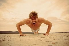 Sport and fitness. Power. Morning exercise outdoor. Full of energy. Man doing push ups exercise in fitness gym. Athletic stock photography