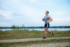 Sport and fitness runner man doing outdoors training for marathon run. Guy doing high intensity interval training sprint workout along lake in summer. Male royalty free stock images