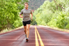 Sport and fitness runner man running on road. Training for marathon run doing high intensity interval training sprint workout outdoors in summer. Male athlete Stock Image