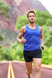 Sport and fitness runner man running on road. Training for marathon run doing sprint interval workout outdoors in summer. Male athlete sports model fit and Stock Photo