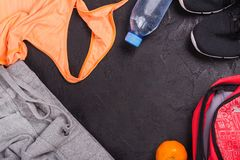 Sport or fitness set with female clothing, dumbbells, bag and sport shoes on black background. Flat lay style. Copy space Stock Image