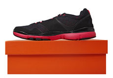 Sport fitness shoe. Fun black and pink leather fitness sport shoe on the orange box isolated over white Royalty Free Stock Image
