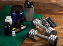 Sport and Fitness Supplement, dumbbells on wood background Stock Image