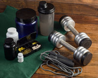 Sport and Fitness Supplement, dumbbells on wood background Royalty Free Stock Photography