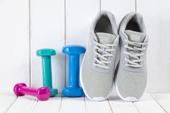 Sport and fitness symbols - sneakers, and colorful dumbbells on. White wooden wall background royalty free stock photo