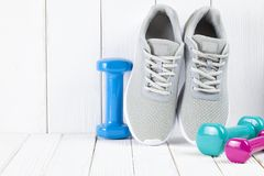 Sport and fitness symbols - sneakers, and colorful dumbbells. On wooden wall background royalty free stock photos