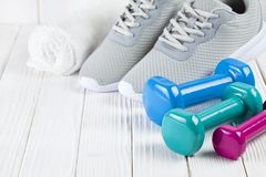 Sport and fitness symbols - sneakers, and dumbbell on wooden wall background. Sport and fitness symbols - sneakers, and dumbbell on white wooden wall background royalty free stock photos