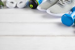 Sport and fitness symbols - sneakers, water and dumbbell on wood. Sport and fitness symbols - sneakers, water and dumbbell on white wooden wall background stock images